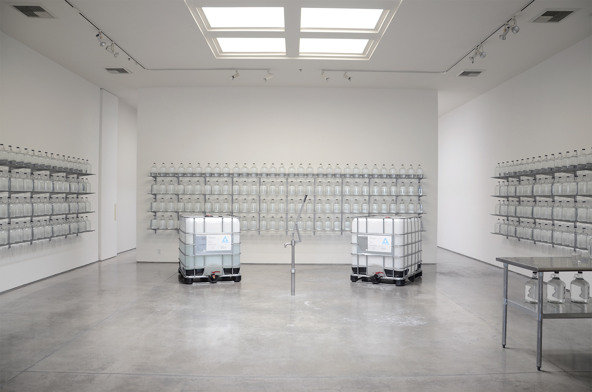 "Iñigo Manglano-Ovalle, Well 34°01'03""N - 118°29'12""W, 2015, 500 gallons of water from Santa Clara Pueblo, glass bottles, shelves and pump, dimensions variable"