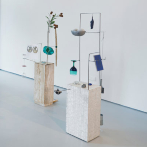 Laura Davis, Cups and Balls (Warm Marble and Cool Shell), 2014, Travertine marble pedestal, brass, steel, plastic bag, vintage political button, plastic thistle, wooden candles, felt, paper, paint, wine glasses, clay, rhinestones, books, string, agate, glue, microbeads, page from a Sotheby's catalogue. Wood, mother of pearl wall covering, steel, wineglasses, resin, mylar, leather, glass paperweight, paper, paint, necklace, plastic Stonehenge pieces, bottle, cement, rhinestone, clay, pewter bowl, sequins, fake flocked rocks, earring backs, each 53 x 14 x 14 inches
