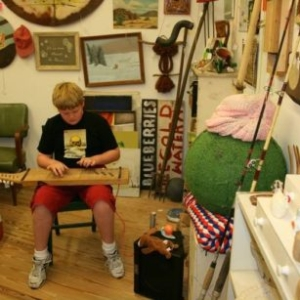 Bill Davenport, Bill's Junk: Young man tries out a handmade electric dulcimer, 2009, mixed media, variable