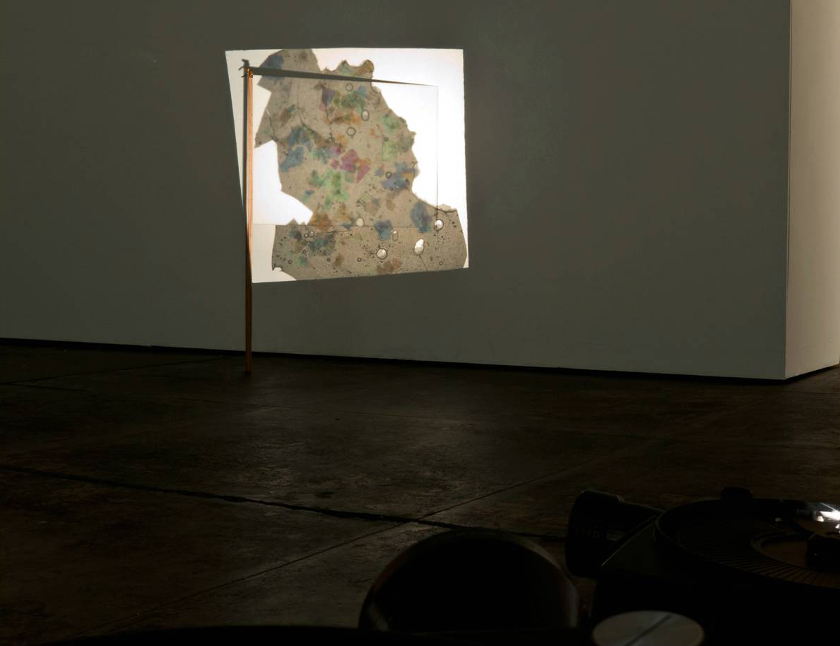 Jillian Conrad, Flag, 2012, opal shards, projector, plexi, variable