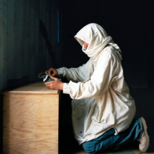 """Claire Beckett, Army Specialist Gary McCorkle playing the role of """"Jibril Ihsan Hamal,"""" a key member of the leading terrorist group in town, Islamic Army of Iraq, with an IED, Medina Wasl Village, National Training Center, Fort Irwin, CA, 2009, 2009, archival inkjet photograph, 30 x 40 inches"""