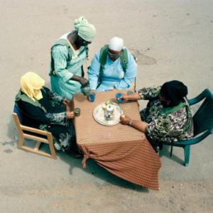 "Claire Beckett, American civilians playing the role of Iraqi village women drinking tea: Karen Davis as ""Salihah Asad Hatim,"" Verna Pouesi as ""Amira Rough,"" Randa Matgyo as ""Kawthar Amid,"" and Faye Ugapo as ""Rim Duqaq Barakah,"" Medina Wasl Village, National Training Center, Fort Irwin, CA 2009 , 2009, archival inkjet photograph, 30 x 40 inches"