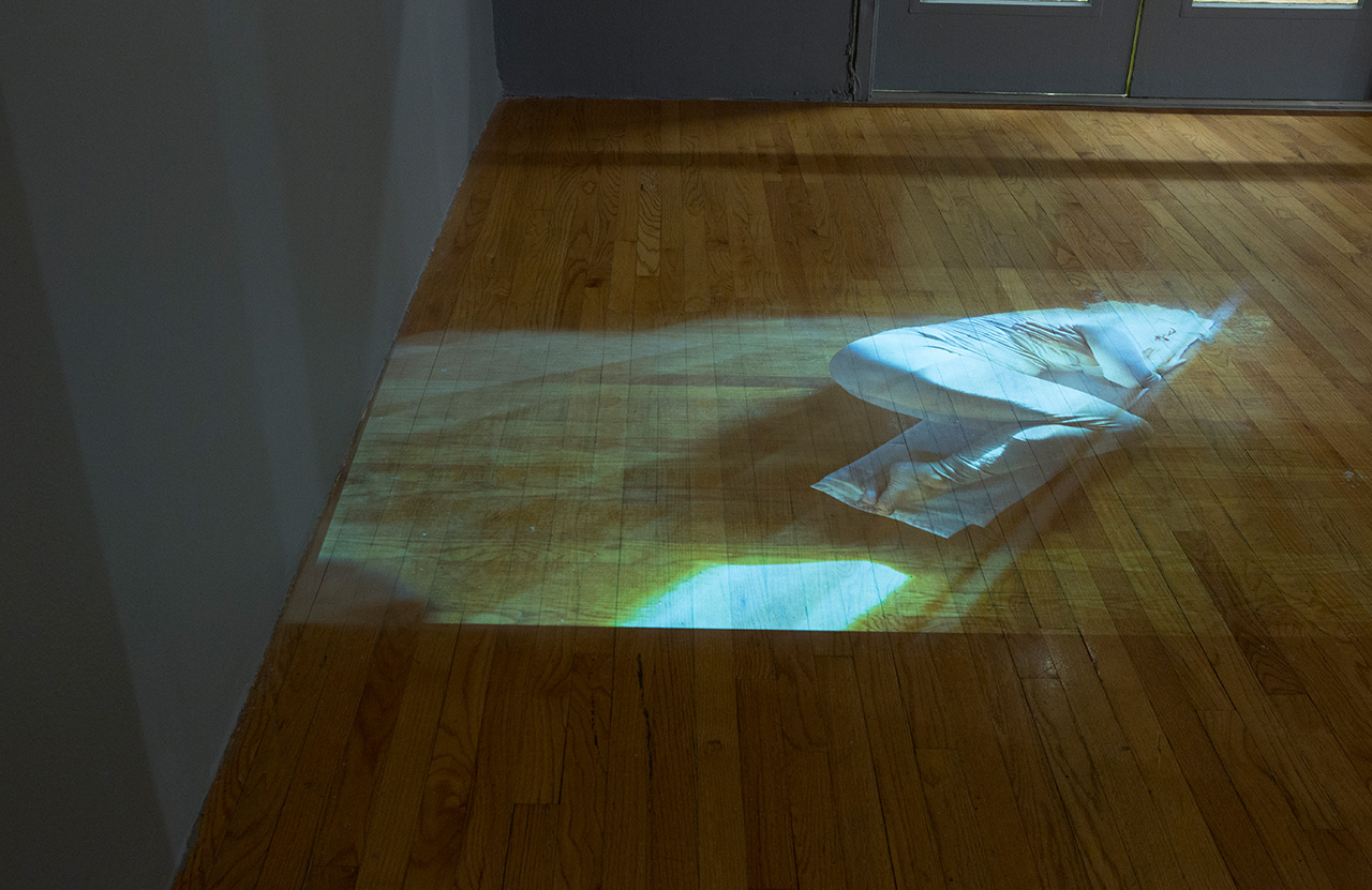 Paola Cabal, Synopsis, 2015, 71 projected still images and spray paint on floor, dimensions variable