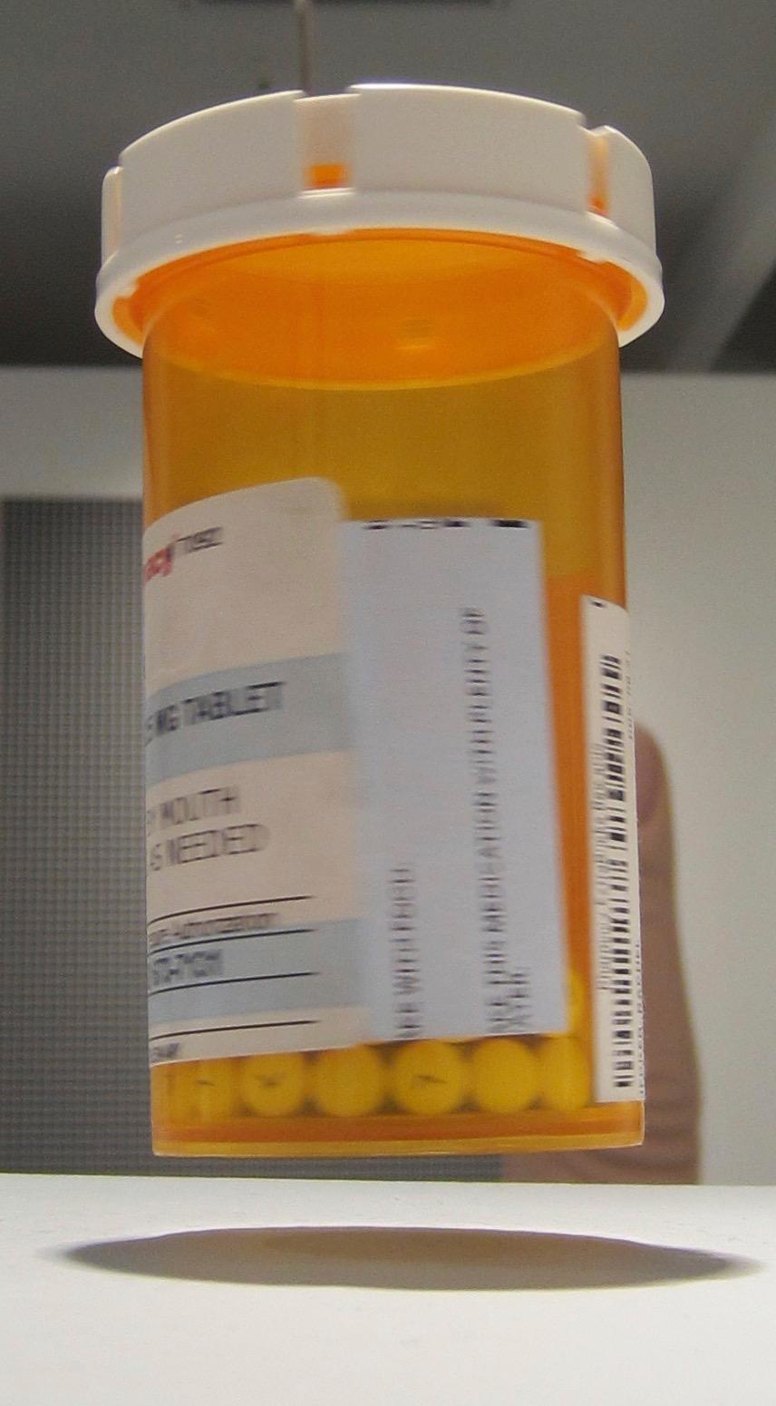 Rachel Hecker, Floating Xanax, (detail), 2013 / 2015, pill bottle, pills, magnet, electromagnet, plastic, wood, 44 x 11 x 11 inches