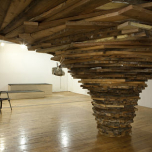 A. Laurie Palmer, Hole, 2010—2012, Recycled wood from torn-down houses, dimensions variable; stacked layers are built to rise and expand centrifugally until the structure is constrained by the walls of whatever space it occupies. (pictured: 7 x 17 x 17 feet
