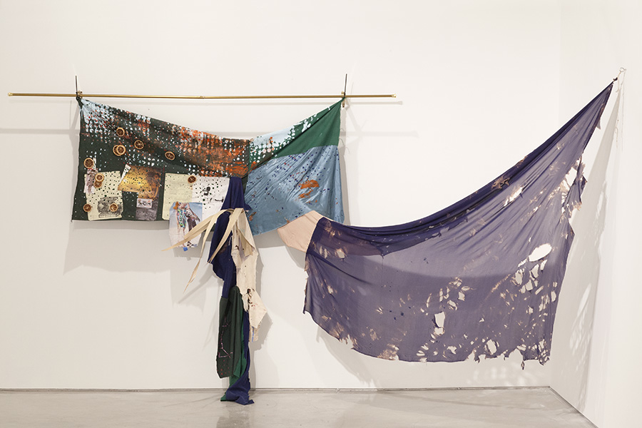 Eric Mack, Claudine, 2014, acrylic on cotton, silk, dried orange slices, palm, legal pad paper, fashion images on a curtain rod, 192 x 72 x 24 inches
