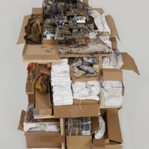 """Kathryn Spence, Untitled, 2011-2012, cardboard, plywood, thread, ink, bobby pins, pillow feathers, towel scraps, clothing remnants, paper, safety pins, bed sheets, """"How to Wash"""" labels, """"Do Not Remove"""" labels, upholstery and mattress tags, photographs, magazines, paper towels, cell phone advertisements, toy squirrel, Styrofoam, string, cotton batting, 42 × 30 × 30 inches. Image courtesy of Wirtz Art"""