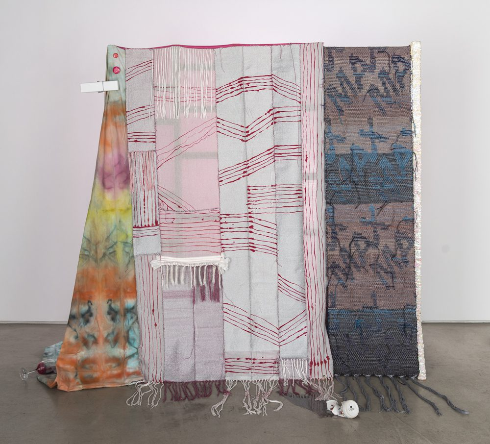 Josh Faught, Max, 2014, Hand woven silver lamé and hemp (hand dyed in colors to match the 2013/2014 fashion forecast), nail polish, sequin trim, coffee spill (resin) with broken Cathy mug, wine spill (resin), giant clothespin, denim, silk, and toilet paper on Cedar support, 68 x 65 x 12 inches